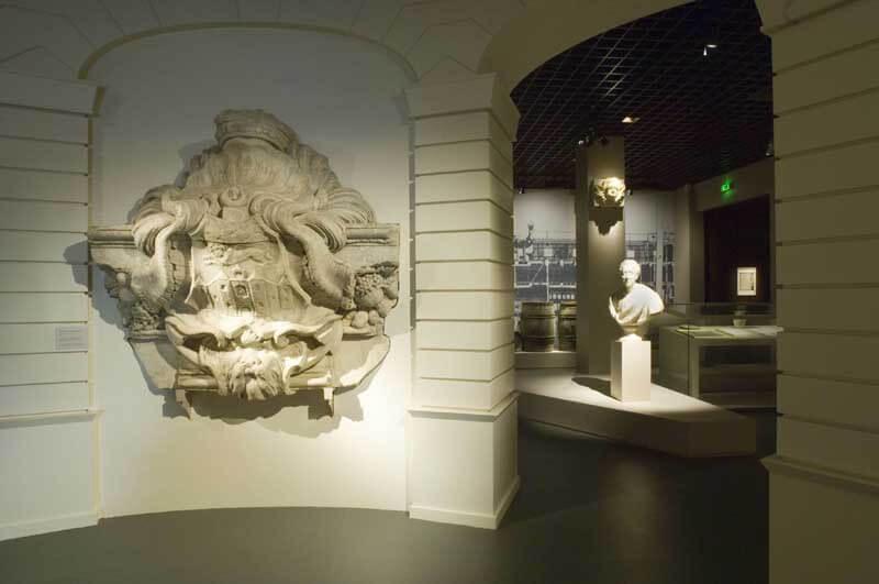 Salle « La ville de Bordeaux au 18e siècle » : écusson aux armes de la ville sculpté par Francin pour le piédestal de la statue équestre de Louis XV qui était située place Royale (aujourd'hui place de la Bourse), en arrière-plan, le buste de Montesquieu